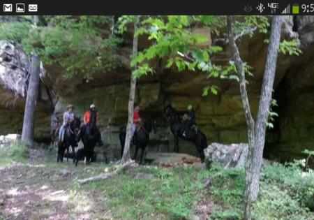 Rider trailriding horses under mossy bluffs at Giant City State Park